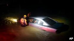 6일 미국령 푸에르토리코의 파자르도 섬에서 구조대가 홍수로 침수된 자동차 안에 생존자가 있는지 살피고 있다.