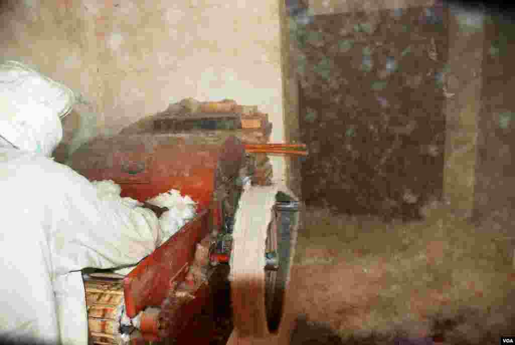 مشین کے ذریعے روئی دھنکنے میں مصروف ایک کاریگر