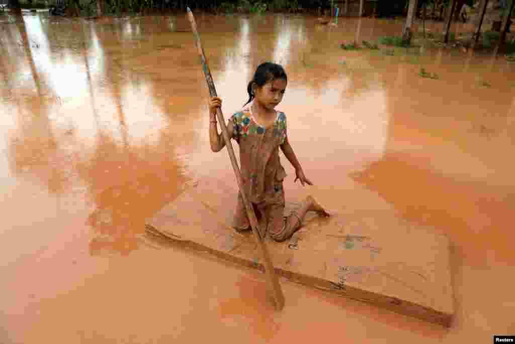 یک دختر بچهدر لائوس برای عبور از گل و لای ناشی از جاری شدن سیلاب در آن منطقه از تشک خواب به عنوان قایق استفاده می کند.
