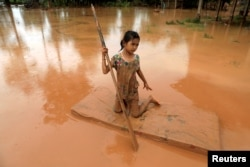 A girl uses a mattress as a raft during the flood after the Xepian-Xe Nam Noy hydropower dam collapsed in Attapeu province, Laos