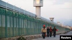 幾名工人從新疆再教育營的外圍圍欄走過。 (2018年9月4日)
