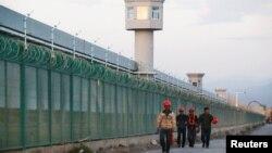 几名工人从新疆再教育营的外围围栏走过。(2018年9月4日)