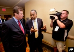 Donald Trump campaign chief Paul J. Manafort, left, chats with former presidential candidate Ben Carson as they head to a 'Trump for president reception' at the Republican National Committee Spring Meeting, April 21, 2016, in Hollywood, Florida.