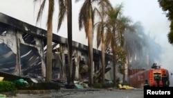 Nhân viên cứu hỏa ngồi nghỉ gần một nhà máy sản xuất giày của Trung Quốc bị hư hại sau các vụ biểu tình bạo động ở Bình Dương, ngày 14/5/2014.