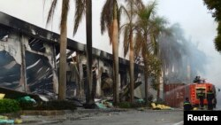 Para petugas pemadam kebakaran beristirahat dekat pabrik sepatu China di provinsi Binh Duong, Vietnam, yang dibakar oleh massa (14/5).