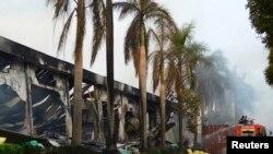 Petugas pemadam kebakaran berusaha memadamkan pabrik sepatu China di Binh Duong, Vietnam selatan yang dibakar massa, Rabu (14/5).