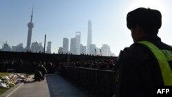 FILE - A security guard watches as mourners place flowers and burn incense at the site of a New Year's Eve stampede at the Bund in Shanghai, China, Jan. 2, 2015.