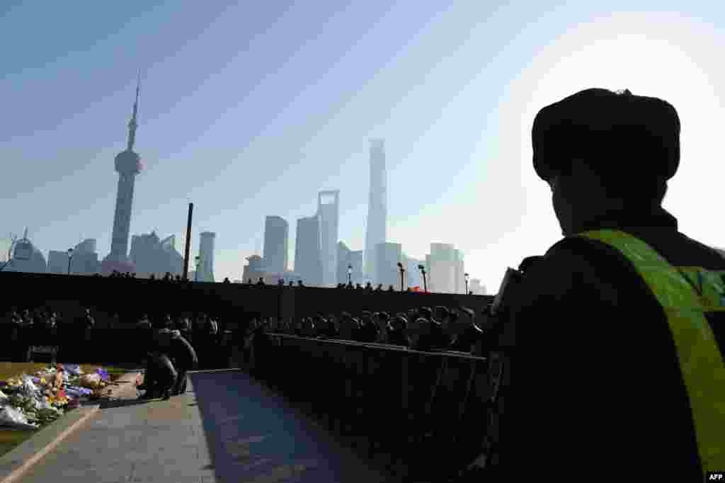 A security guard watches as mourners place flowers and burn incense at the site of a New Year's Eve stampede at the Bund in Shanghai, China. The stampede, shortly before midnight on the city's historic waterfront, killed at least 36 revelers.