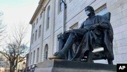 美国哈佛大学校园里的约翰·哈佛塑像,疫情之下有人为他戴上了口罩。(2020年3月14日)