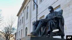 The John Harvard statue at Harvard University, a popular tourist attraction at the campus in Cambridge, Mass, sits adorned with a medical mask as students prepared to leave campus, Saturday, March 14, 2020.