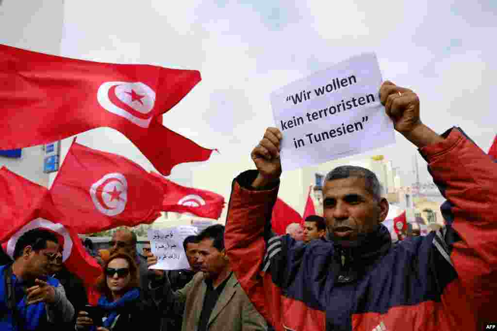 "Tunisians wave banners and their national flag during a demonstration in Midoun, northeast of Djerba, two days after gunmen attacked the National Bardo Museum. The attack which killed 21 people, was the country's worst since the 2011 uprising that toppled leader Zine El Abidine Ben Ali. German writting on placard reads: ""We don't want any terrorists in Tunisia."""