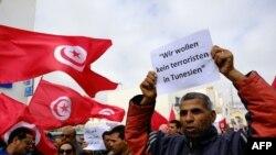 Người Tunisia giương cờ và biểu ngữ 'Chúng tôi không muốn có bất cứ phần tử khủng bố nào ở Tunisia' trong cuộc biểu tình hôm 20/3/15 2 ngày sau khi các tay súng tân công Viện Bảo tàng Quốc gia Bardo