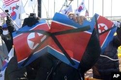 여자아이스하키 남북 단일팀이 스웨덴과 평가전을 치룬 4일 경기장 밖에서 시위대가 북한 인공기를 찢고 있다.