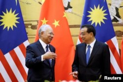 FILE - Malaysia's Prime Minister Najib Razak and China's Premier Li Keqiang attend a signing ceremony at the Great Hall of the People, in Beijing, China, Nov. 1, 2016.