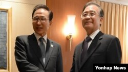 19일 캄보디아 프놈펜에서 열린 한.중 정상회담. 악수하는 이명박 대통령과 중국 원자바오 총리(오른쪽).