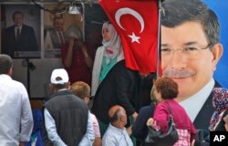 FILE - People walk past a poster of Turkey's Prime Minister and leader of the Justice and Development Party (AKP) Ahmet Davutoglu (R) in Istanbul, Turkey, June 5, 2015.