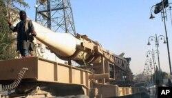 Chiến binh Nhà nước Hồi giáo trong diễu hành với một tên lửa ở Raqqa, Syria.