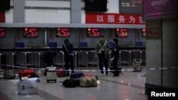 Cảnh sát Trung Quốc đứng cạnh các hành lý còn lại tại phòng vé ở nhà ga sau vụ tấn công đẫm máu, ngày 2/3/2014.