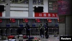 Saldırının ardından Kunming tren istasyonunda bavulların başında bekleyen polis
