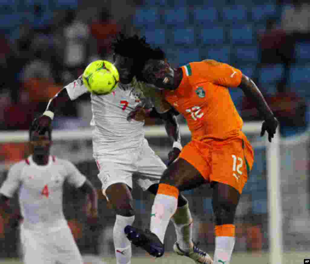 Bony of Ivory Coast fights for the ball with Rouamba of Burkina Faso during their African Nations Cup soccer match in Malabo