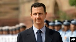 FILE - Syrian President Bashar al-Assad inspects a guard of honor at the Presidential Palace in New Delhi, India, June 18, 2008.