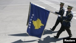 Members of Kosovo Security Force march with a flag of Kosovo (front)