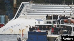 Relatives of victims stand on a ferry in front of the capsized cruise liner Costa Concordia outside Giglio harbor, Italy, January 13, 2013.
