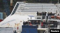Para penyintas dan keluarga korban musibah kapal Costa Concordia berdiri di dalam sebuah kapal ferry yang berhenti di dekat kapal pesiar yang teronggok di dekat pelabuhan Giglio, Italia, untuk memperingati setahun tenggelamnya kapal pesiar tersebut (13/1).