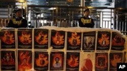 Người biểu tình cầm biểu ngữ lớn với hình ảnh của những người Tây Tạng đã tự thiêu bên ngoài Văn phòng Liên lạc của Trung Quốc tại Hồng Kông.