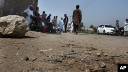 Pakistani police officers and local residents gather at the site of firing incident at Garhi Sohbat Khan on the outskirts of Peshawar, Sept. 18, 2016. Two gunmen on a motorcycle killed three soldiers Sunday, police said.