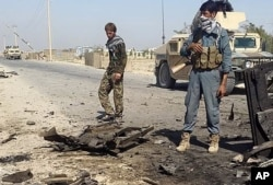 Afghanistan's security forces inspect the site of a U.S. airstrike in Kunduz city, north of Kabul, Afghanistan, Oct. 1, 2015.