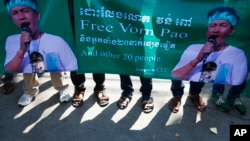 Posters printed with a detainee Vorn Pao, a Boeung Kak lake activist, is holding by protesters stage in front of the Appeals Court during a rally, in Phnom Penh, Cambodia, Monday, March 24, 2014. The rally took place on Monday demanding the release of 21