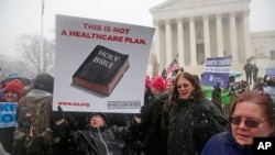 Beth Corbin holds a poster during a demonstration in front of the Supreme Court in Washington, Tuesday, March 25, 2014, as the court heard oral arguments in the challenges of President Barack Obama's health care law requirement that businesses provide their female employees with health insurance that includes access to contraceptives.