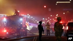 The National Guard standby as firefighters extinguish a blaze at a gas station Friday, May 29, 2020, in Minneapolis. Protests continued following the death of George Floyd, who died after being restrained by Minneapolis police officers on Memorial Day. (AP Photo/Julio Cortez)