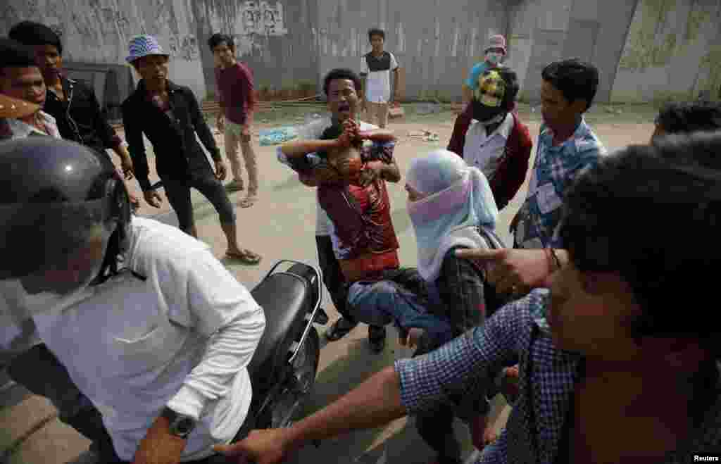 An injured garment worker is helped by his colleagues after clashes broke out during a protest in Phnom Penh, Jan. 3, 2014.