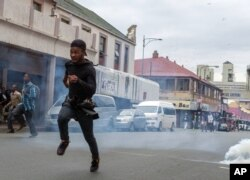 Members of the ANC Youth League flee from teargas and rubber bullets fired by police, at the end of a march by the main opposition Democratic Alliance party in Johannesburg, April 7, 2017.