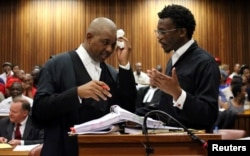 Advocate Dali Mpofu (L) reacts as he chats to Advocate Tembeka Ngcukaitobi during court hearing arguments on a report into allegations of political interference by wealthy friends of President Jacob Zuma, at the North Gauteng High Court, in Pretoria, Nov.