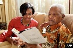 Đệ nhất phu nhân Hoa Kỳ Michelle Obama đến thăm cựu Tổng thống Nam Phi Nelson Mandela tại ngôi nhà của ông trong thành phố Houghton, 2011 (AP Photo/ Nelson Mandela Foundation)