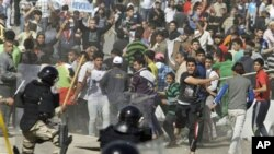 Iraqi anti-government protesters throw stones and trash at riot police during a demonstration in Baghdad, Iraq, Friday, Feb. 25, 2011. Thousands marched on government buildings and clashed with security forces in cities across Iraq on Friday, in the large