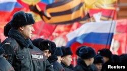 Cảnh sát đứng trước những người tham gia cuộc biểu tình chống cuộc nổi dậy năm 2014 ở Ukraine, tại Moscow, 21/2/2015.