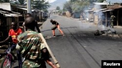 Un homme dégage une barricade alors que les soldats patrouillent dans une rue de Bujumbura, Burundi 15 mai 2015. REUTERS/Goran Tomasevic.
