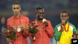 Gold medallist Samuel Kamau Wanjiru of Kenya (C), silver medallist Jaouad Gharib of Morocco (L) and bronze medallist Tsegay Kebede of Ethiopia pose for victory ceremony at the Beijing 2008 Olympic Games (File Photo - August 24, 2008)