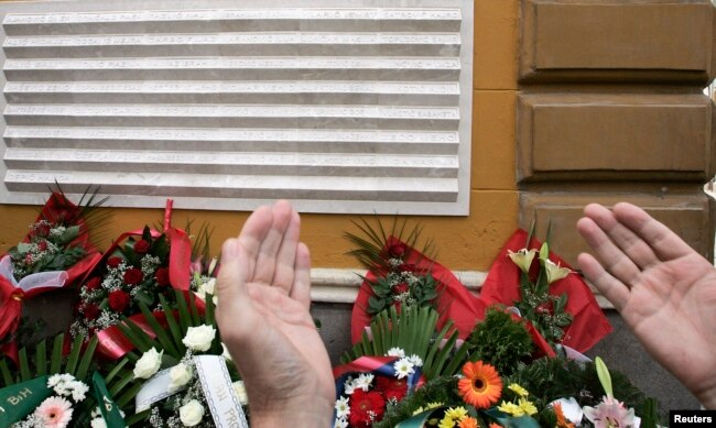 FILE - A Bosnian man prays in front of a memorial plague during the 13th anniversary