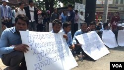 """A group of former bus drivers of Capitol Tours Cambodia company on Monday, February 8, 2016, held banners showing the demand for justice for Norn Vanna, a former bus driver of Capitol Tours Cambodia company and Ros Siphay, a member of the Cambodian Labor Confederation who were arrested by authorities in Phnom Penh's Prampi Makara district on Saturday, February 6, 2016 and sent the Phnom Penh Municipal Court on Monday, February 8. They both were detained by the court on Monday on charges of """"intentional violence, opposing public officials, and obstruction to public traffic."""" (Hul Reaksmey/VOA Khmer)"""