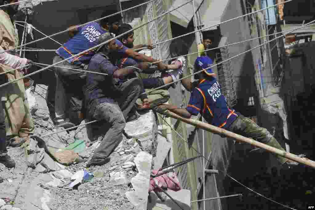 Pakistani volunteers rescue an injured girl from the remains of a collapsed building in Karachi.