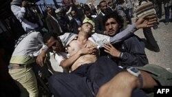 Người biểu tình bị thương được khiêng ra khỏi hiện trường sau vụ đụng độ với lực lượng an ninh Yemen ở Sana'a, ngày 25/10/2011