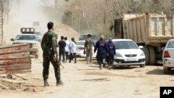 Les forces gouvernementales syriennes supervisant l'évacuation par bus des combattants rebelles et de leurs familles, à un poste de contrôle dans l'est de la Ghouta, en Syrie, sur une hoto publiée par l'agence de presse officielle syrienne SANA le 22 mars 2108.