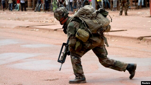 A French soldier crouches while on foot patrol in Bangui, Dec. 8, 2013.
