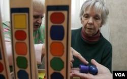 Pasien yang menderita demensia (kanan) mengerjakan teka-teki dengan balok bersama seorang perawat di panti jompo Morning Glory di negara bagian Pennsylvania.