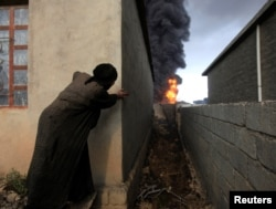 FILE - A woman looks at fire and smoke from oil wells set ablaze by Islamic State militants before the fled the oil-producing region of Qayyara, Iraq, Nov. 4, 2016.